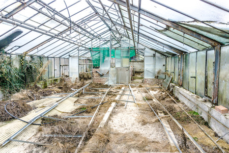 Greenhouse with broken glass, the construction is clearly visible.