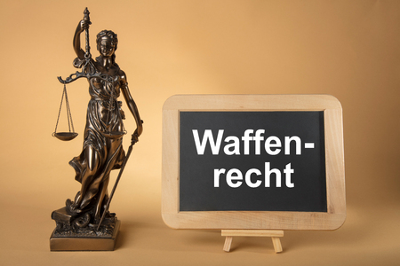Justizia Figure with chalkboard with german text: Weapons Legally on beige Background Stockfoto - 119085355