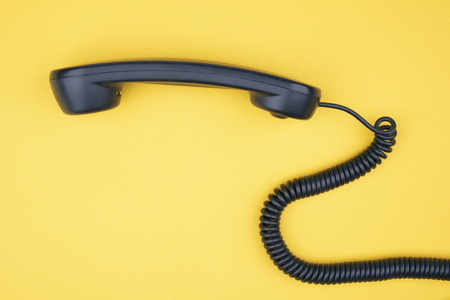 Black Phone Receiver on yellow Background