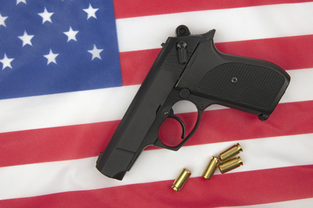 Pistol with ammunition on a american flag as background Фото со стока