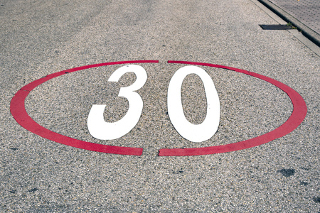 Detail from the Numbers thirty 30 Speed Limit painted on a Street
