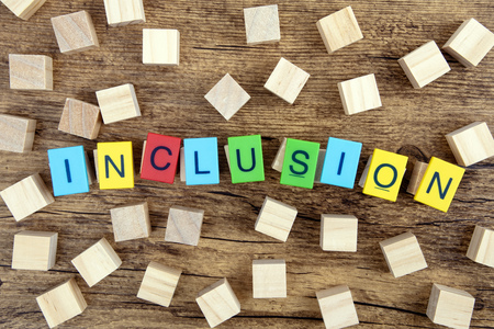 Concept: Inclusion with colorful Toy Letters and wooden cubes on dark background Stockfoto - 119084946