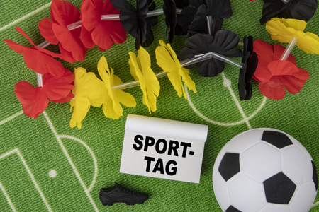 Sporttag german language means Sports Day. Soccer Ball with flower necklace in the colors of german flag and calendar