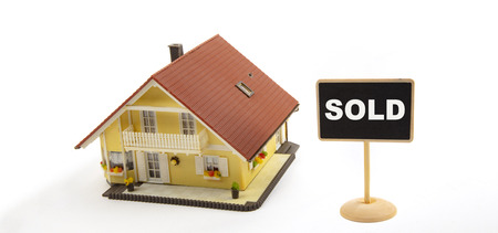 Sold - Concept Business Real Estate with Toy House and little Blackboard Sign on white Background