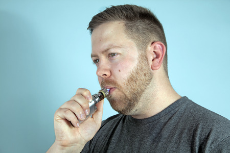 Young man vaping smoking an e-cigarette, he holds the vaporizer in his hand