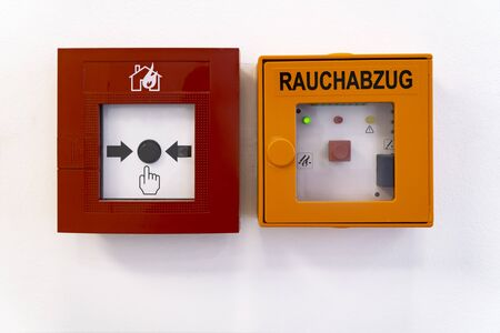 Fire alarm system on the wall in a office building. Rauchabzug in german language means Smoke Flue Banco de Imagens