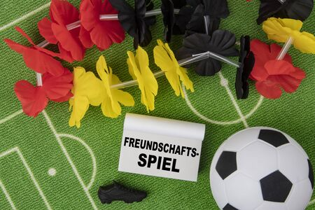 Freundschaftsspiel in german language means Friendly Match. Soccer Ball with flower necklace in the colors of german flag and calendar