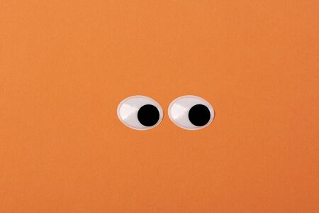 Two funny Toy Eyes on orange Background looking