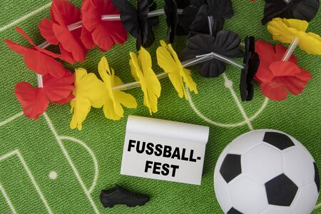 Fussballfest in german language means Soccer Festival. Soccer Ball with flower necklace in the colors of german flag and calendar