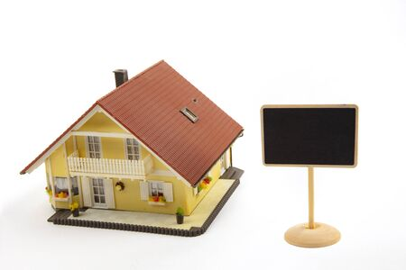 Toy house and little blackboard sign on white background