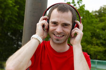 Young joyful Sportsman with red headphones in nature