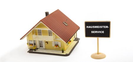 Hausmeisterservice   Janitor Service - Concept Business Real Estate with Toy House and little Blackboard Sign on white Background Stockfoto