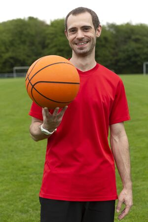 Young friendly man with basketball in soutdoor sports area