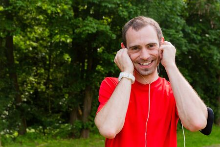 Friendly young sportsman with earphones outdoor in a park Reklamní fotografie