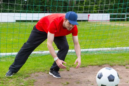 Young man with cap as goalkeeper catching a soccer ball on a soccer field