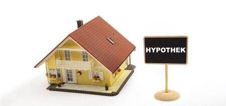 Hypotheke means Mortgage. Concept Business Real Estate with Toy House and little Blackboard Sign on white Background