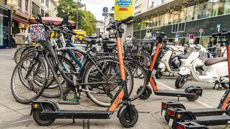 Frankfurt, Germany - OCTOBER 5th 2019: Group of E-scooters and bicycle Eco friendly mobility for urban lifestyle by sharing Electric Scooter, park on shady sidewalk in city. 報道画像