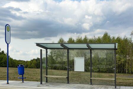 Arrêt de bus moderne avec poubelle avec ciel nuageux Banque d'images