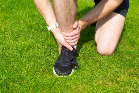 Man hold his ankle because of pain after sprain