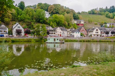 Idyllic Lahn River with wooden House Boat in Germany