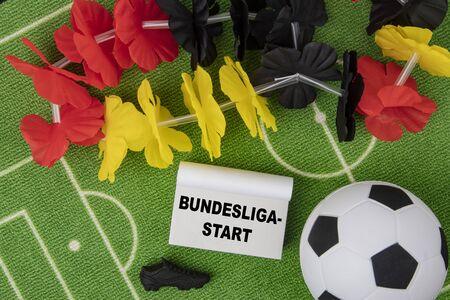 Soccer Ball with flower necklace in the colors of german flag and calendar. Bundesliga Start in german language means Bundesliga Opener