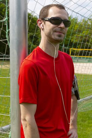 Friendly young sportsman with sunglass and earphones outdoor in a park