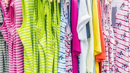 Shop offers colorful clothes in front of a shop Stock Photo