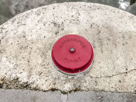 Red Measuring Point on cement ground in germany 写真素材