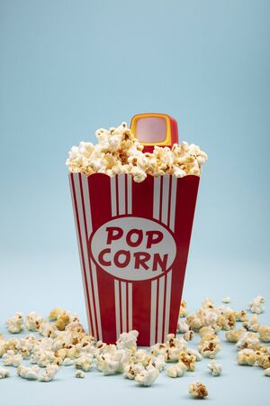Crunchy Popcorn with Toy Televison on bright blue background