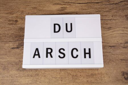 Concept DU ARSCH means You asshole letters on a lightbox over wooden background