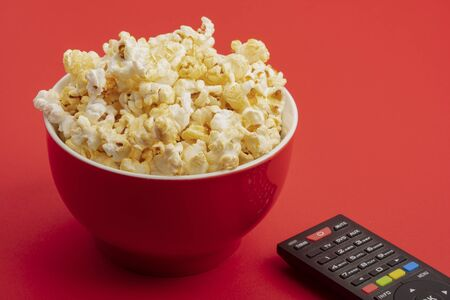 Fresh Popcorn in a red bowl and remote control over red background