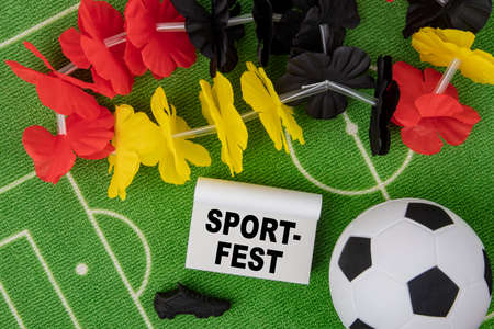 Sport Fest in german language means Sport Event. Soccer Ball with flower necklace in the colors of German flag and calendar Standard-Bild