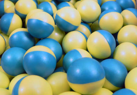 close up of blue and yellow paintballs