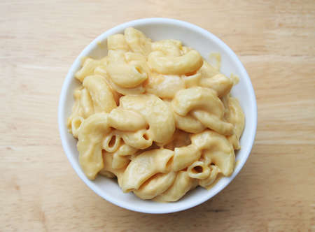 Macaroni and Cheese in a white bowl on a butcher block table photo