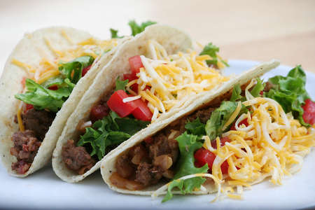 minced beef: Three Ground Beef Tacos on a White Plate