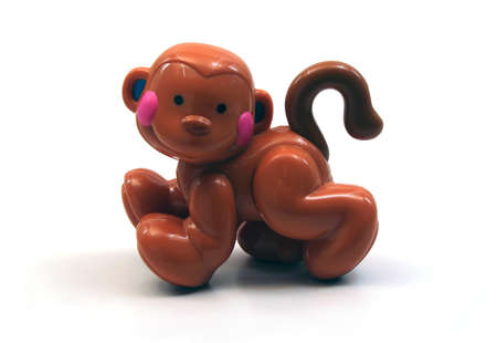 Brown Plastic Toy Monkey on White Background photo