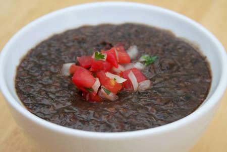 Heerlijke zwarte bonen soep in een witte kom Stockfoto