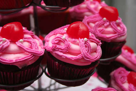Close up of Chocolate Cupcakes with Pink Frosting and Red Candy Topping