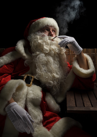 Santa Claus needs a little break and smokes a cigarette. Stressful christmas and advent season.