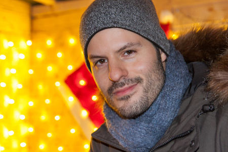 Attractive man smiling and standing at a christmas market Zdjęcie Seryjne