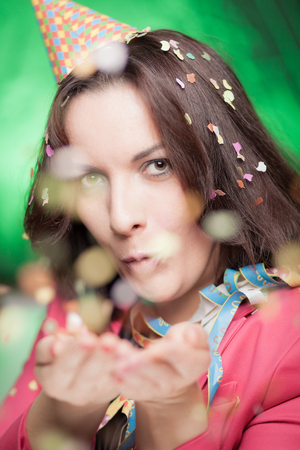 Attractive woman blowing confetti and celebrating something.