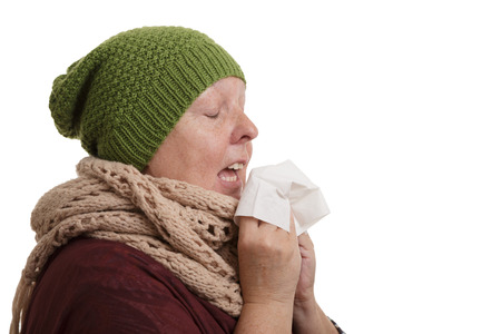 A senior woman in winter time with disease has to sneeze and blow into a handkerchief isolated on white background.