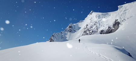 Snowy winter scenery with high moutains and a hiker.