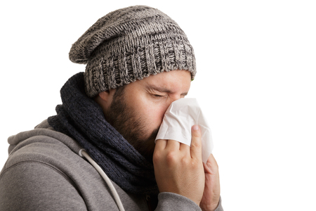 A man in winter time with disease has to sneeze and blow into a handkerchief isolated on white background.