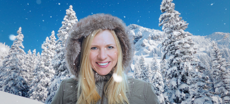 Snowy winter scenery with high moutains and a smiling attractive woman in the foreground.