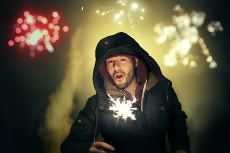 Man celebrating New Years Eve with fireworks.