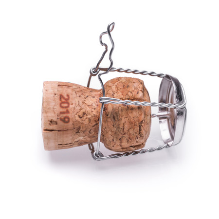 A champagne or sparkling wine cork from 2019 lying on the ground. Isolated on white background.