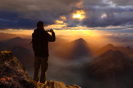 Young male hiker standing on the peak of the mountain Zdjęcie Seryjne