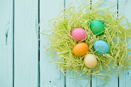 Colorful easter eggs in a nest on a blue wooden background.
