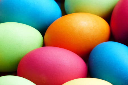 Many colorful eggs in a easter nest close up.
